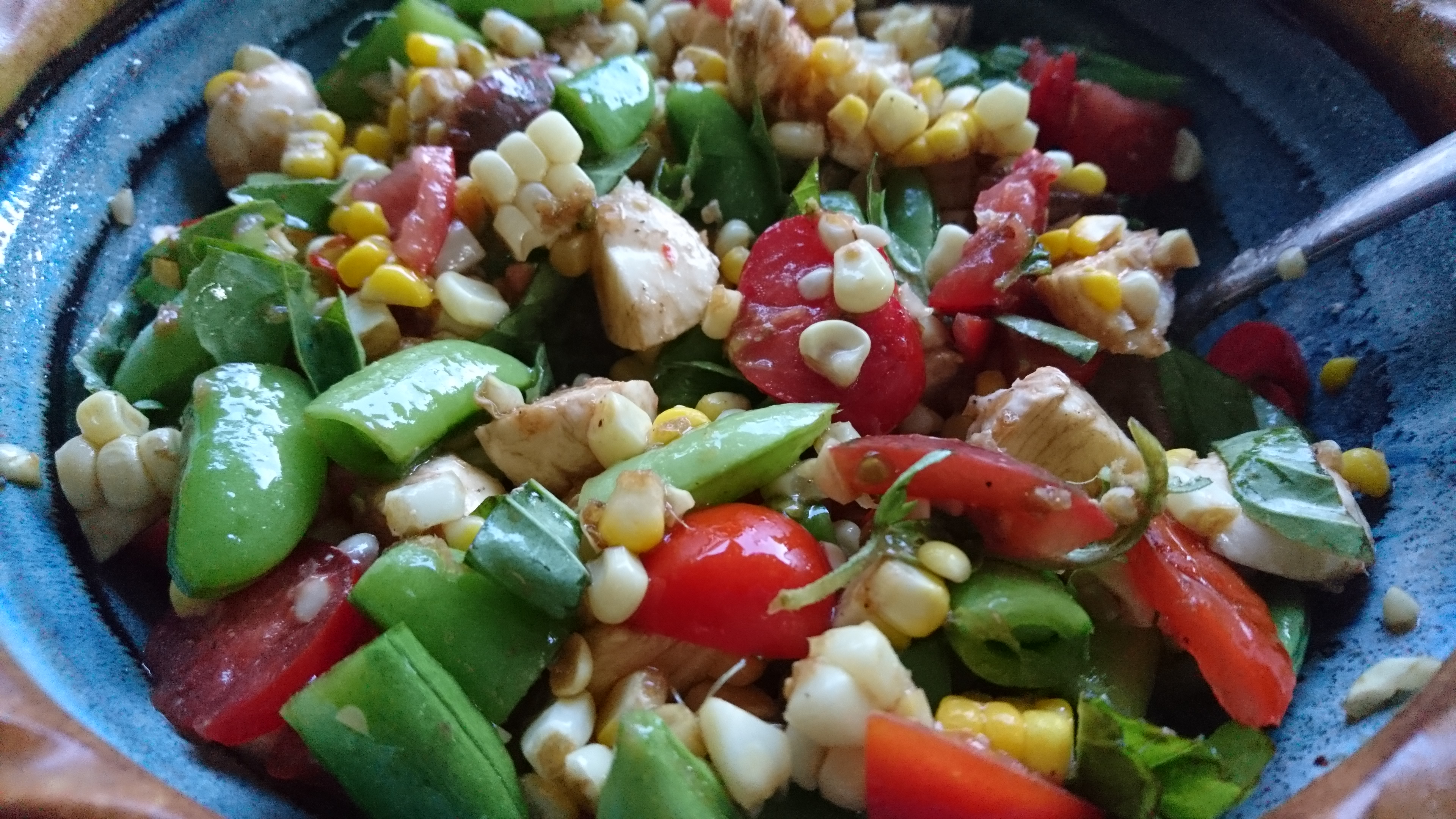 snap pea, tomato, and corn salad in a ceramic bowl
