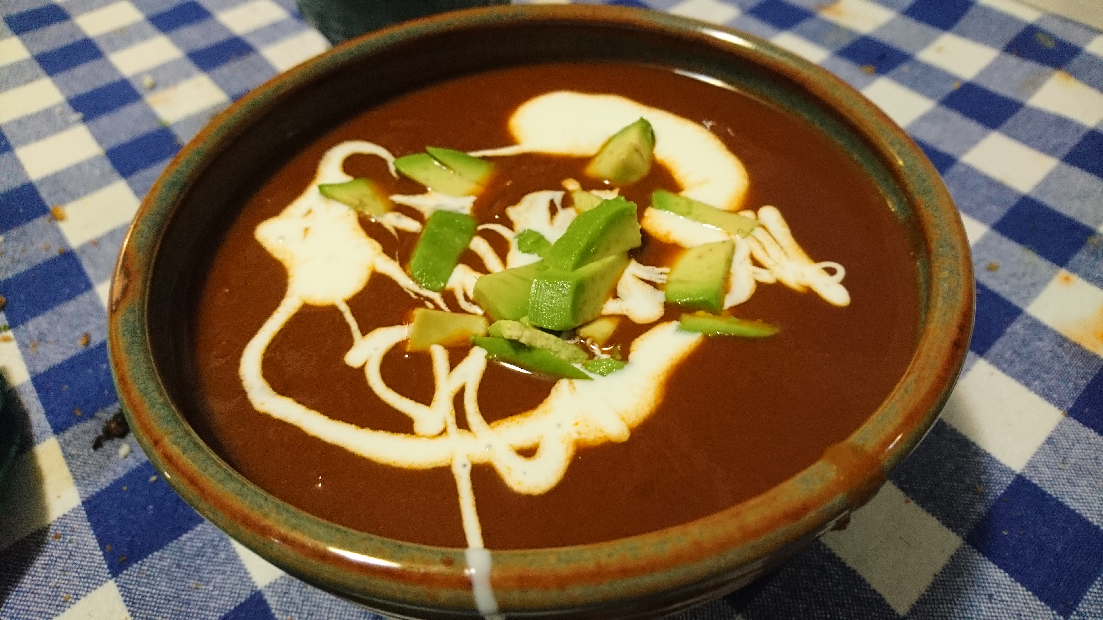 bowl of pinto bean soup with avocado and cream